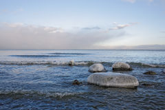 Winter sea landscape. Boulders above a surface of the sea  covered by caps of an ice Stock Images