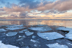 Winter Sea landscape with big ice fragments on water. Winter Sea coastal landscape with big floating ice fragments on still cold water. Gulf of Finland, Russia Stock Photos