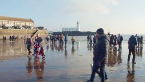 Winter sea swimmers in fancy dress and spectators on the beach.