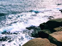 The winter sea wave beat against the rocks royalty free stock photos