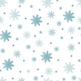 Winter seamless background with flat white snowflakes on a blue Stock Photos