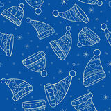 Winter seamless pattern with hats on blue backgrou Stock Images