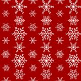 Winter seamless pattern with lines of white snowflakes on red background. New Year backdrop. Vector flat symmetric Christmas ornament for fabric, textile Royalty Free Stock Photos