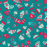 Winter seamless pattern with socks, mittens and ha. Ts on the turquoise background Royalty Free Stock Image