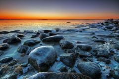 Winter seascape. Frosted beach and rocks with colorful sunrise in early morning Royalty Free Stock Photo