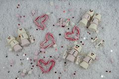 Winter season Christmas food photography using marshmallows shaped as snowman with happy iced on smile in snow with love hearts Stock Photo