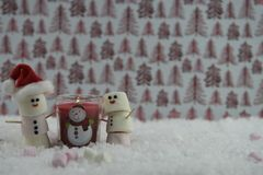 Christmas food photography using marshmallows shaped as snowman with iced on smile and red lit candle all standing in snow. Winter season Christmas photography Royalty Free Stock Image