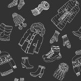 Winter season doodle clothes seamless pattern. Hand drawn sketch elements warm raindeer sweater, coat, boots, socks, gloves and ha Stock Photos