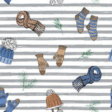 Winter season doodle clothes seamless pattern. Hand drawn sketch elements warm socks, gloves and hats. striped vector background i Royalty Free Stock Images