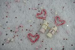 Winter season Christmas food photography using marshmallows shaped as snowman with happy iced on smile in snow with love hearts Stock Images