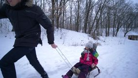 Winter season at forest, father pulls his children on sled on snowy road. Winter season at forest, young father pulls his children on sled on snowy road stock footage