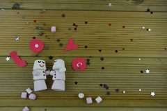 Romantic winter season photography image with marshmallows shaped as sleeping snowman with smiles iced on and word Love in letters Stock Image