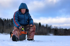 Winter season old man fishing on lake Stock Photography