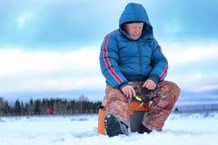 Winter season old man fishing on lake Stock Photo
