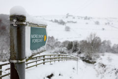 Winter season snow forecast. Country pathway direction sign reading more snow forecast Stock Photography