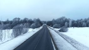 Winter season. Snow forest, aerial shot. Breathtaking natural landscape, frozen forest and dark road go to the forest. Winter season. Snow forest, aerial shot stock footage