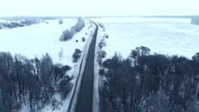 Winter season. Snow forest, aerial shot. Breathtaking natural landscape, frozen forest and dark road go to the forest. Winter season. Snow forest, aerial shot stock video footage