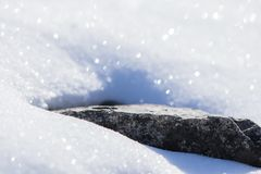 Winter season snowy ground texture glittering in sunlight with isolated rock starring out. Winter season snowy ground texture glittering in sunlight with stock photos