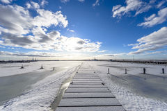 A winter seaview on the pier, by entrance to the port, with froz Royalty Free Stock Photos