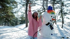Winter selfie, Handy in der Hand einer jungen Frau, die Spaß selfie Foto im Winterwald hintergrundbeleuchtet macht stock video footage