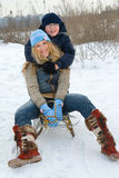 Winter serie. Beautiful girl sitting on the sledge with her small brother Royalty Free Stock Photography