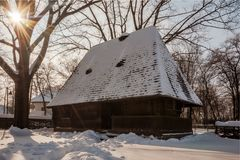 Sun shines over a snow covered traditional wooden homestead Stock Photo