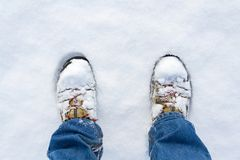Winter shoes footprint in fresh snow, blue jeans trousers, copyspace. Top view of winter shoes footprint in fresh snow, blue jeans trousers, white copyspace Stock Photos