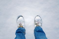 Winter shoes footprint in fresh snow, blue jeans trousers, copyspace. Top view of winter shoes footprint in fresh snow, blue jeans trousers, white copyspace Stock Image