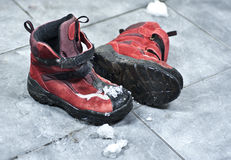 Winter shoes making a mess in the entrance. A pair of winter shoes full of snow making the entrance floor messy Royalty Free Stock Images