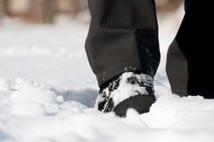 Winter shoes in snow. Winter shoes with black pants in snow Stock Photos
