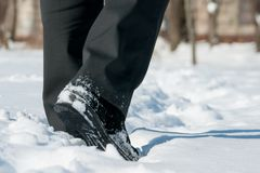 Winter shoes in snow. Winter shoes with black pants in snow Stock Image