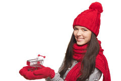 Winter shopping concept. Closeup of smiling beautiful woman in winter red hat and scarf holding small empty shopping basket on her palms, over white background Royalty Free Stock Image