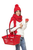 Winter shopping. Concept. Smiling beautiful woman in winter red hat and scarf holding empty shopping basket showing blank credit card over white background Royalty Free Stock Photo