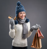 Winter shopping. Image of a young winter lady in warm wearing with shopping bags and a credit card in hands over grey Royalty Free Stock Photos