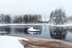 Winter shore of unfrozen lake with melted water Royalty Free Stock Image