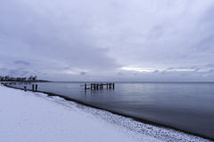 Winter shoreline with broken pier posts standing in tranquil sea Stock Photo