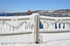 Winter shoreline, ice curtains dangle from rope fence in foregro Royalty Free Stock Image