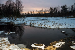Winter Siberian landscape. The river does not freeze in winter.Late in the evening. Stock Images