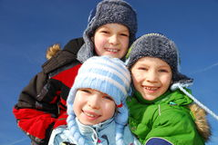 Winter siblings. Three happy smiling caucasian white kids in winter clothes staring Stock Photo