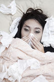 Winter sick. Beautiful woman is laying down on her bed due to her illness in winter Stock Photos