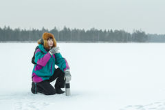 Winter sitting on haunches hiker with metal drink flask resting at snowy landscape background Royalty Free Stock Photography