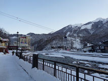 Winter ski resort Krasnaya Polyana, Russia. People walk along snow embankment, cableway over the river, high mountains with ski slopes Stock Image