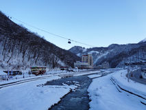 Winter ski resort Rosa Khutor, Russia. Snow-covered Caucasus mountains, hotels on the embankment of the river, much snow Stock Image