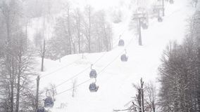 Winter ski resort with ski lifts on mountain. Ski slope with ski lifts and runs in foggy weather. Active holidays in. Winter stock video footage