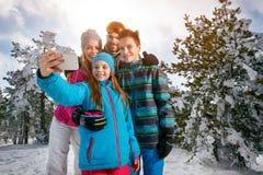 Winter, ski, snow and fun - family enjoying ski holiday. Mobile. Winter, ski, snow and fun – smiling family enjoying ski holiday. Mobile photo. Selfie Royalty Free Stock Image
