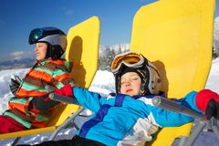 Winter, ski, sun and fun. Winter, ski, sun and fun - portrait of kids in winter resort resting in the deck chair Royalty Free Stock Images