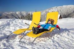 Winter, ski, sun and fun. Winter, ski, sun and fun - happy boy skier in winter resort resting in the deck chair Stock Photos