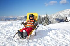 Winter, ski, sun and fun. Winter, ski, sun and fun - happy girl skier in winter resort resting in the deck chair Stock Image