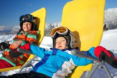 Winter, ski, sun and fun. Winter, ski, sun and fun - portrait of kids in winter resort resting in the deck chair Stock Photos
