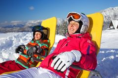 Winter, ski, sun and fun. Winter, ski, sun and fun - Portrait of mother with her daughter in winter resort resting in the deck chair Royalty Free Stock Photos